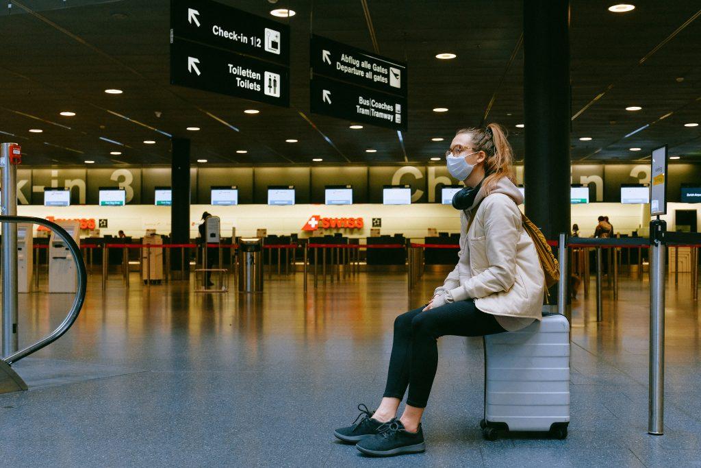 Frau mit Mundschutz am Flughafen